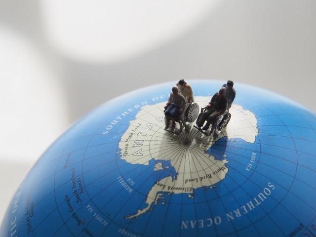 地球儀の上にある介護されている老人と介護士の人形