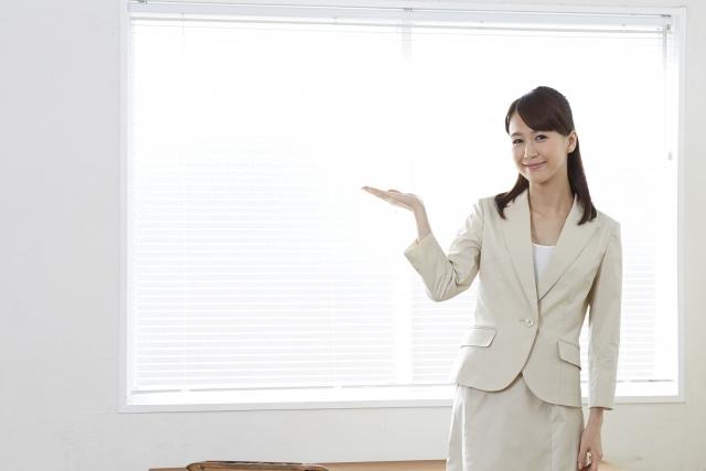 ブラインドの前で説明する女性